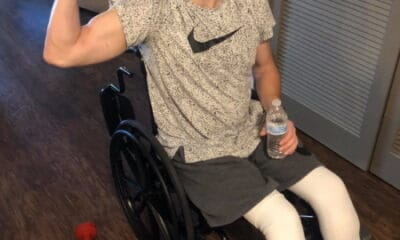 Adam Troutman sits on his wheelchair while wearing a grey Nike shirt and holding a water bottle with one hand and showing his muscle with another hand.