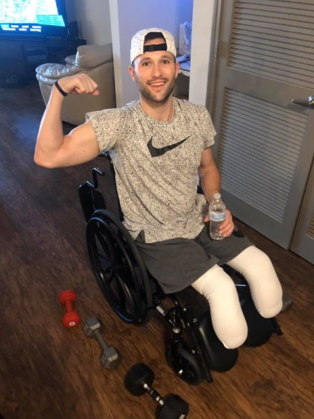 Athlete, Adam Troutman, sitting in a wheelchair flexing his right arm.