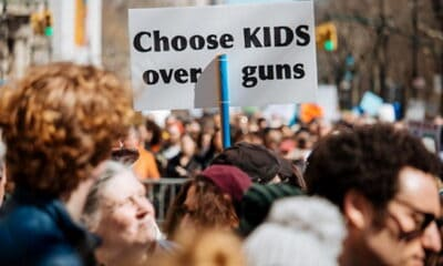"A big crowd of people protesting outside of a building, while one person wearing a hat carries a sign saying, ""Choose KIDS over guns."""
