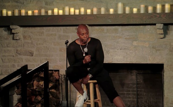 Comedian, Dave Chappelle, wearing an all black outfit, sitting on a stool, while presenting his take on the black lives matter movement.