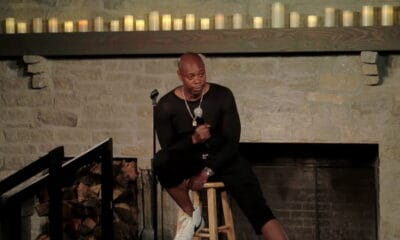 Famous comedian Dave Chappelle, wearing an all black outfit, sitting on a brown stool, while opening up on his take on the black lives matter movement.