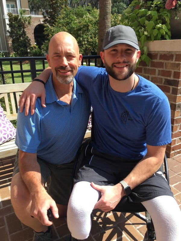 Athlete, Adam Troutman, wraps his arm around his dad while sitting outside, and both wearing blue.