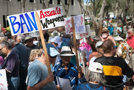 A big crowd of people, majority wearing hats, protest outside of a building against gun violence.