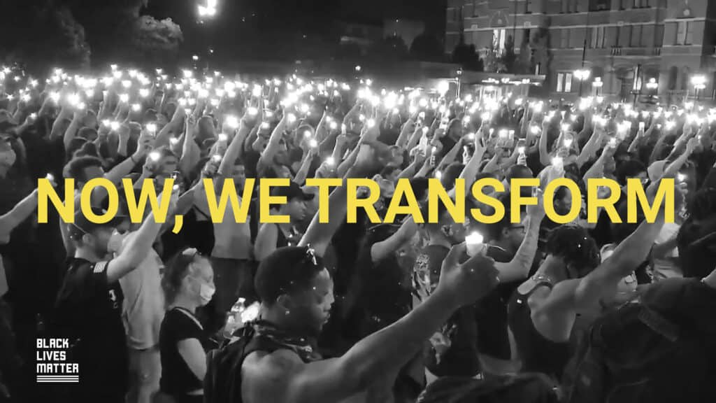 """People holding candles at a BLM event, with caption """"now, we transform"""""""