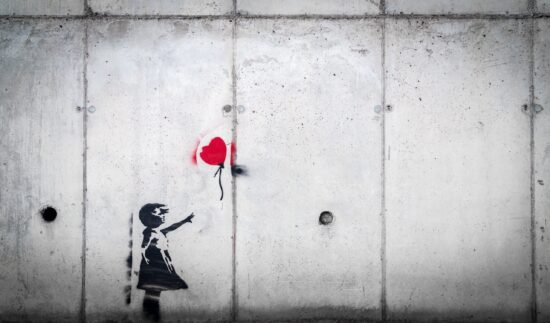 Mural of a little girl letting go of a red heart-shaped balloon.