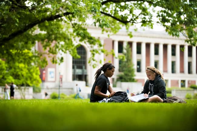 Students sitting and reading in a field on a university's campus