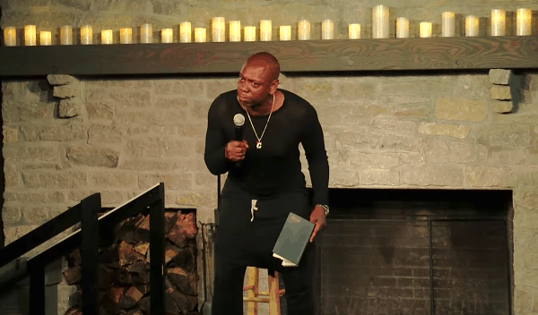 Comedian, Dave Chappelle, wearing an all black outfit, sitting on a stool, holding a microphone.