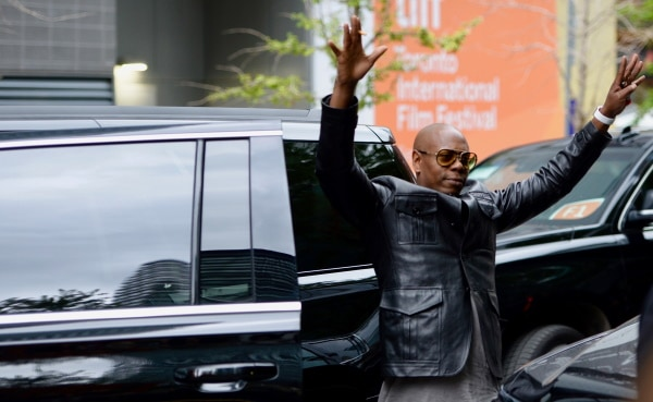 Comedian, Dave Chappelle, wearing a black leather jacket and glasses waves his hands in the air in front of a black car outside.