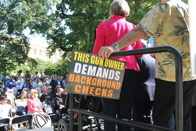 "A lady with short grey hair wearing a pink sweater and a man wearing a beige shirt carry a sign saying, ""This gun owner demands background checks."""