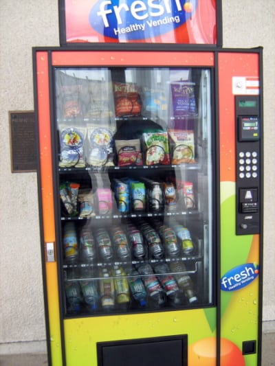 """A vending machine called """"fresh Healthy Vending"""" with a background of different fruit mixed together with the slots full."""