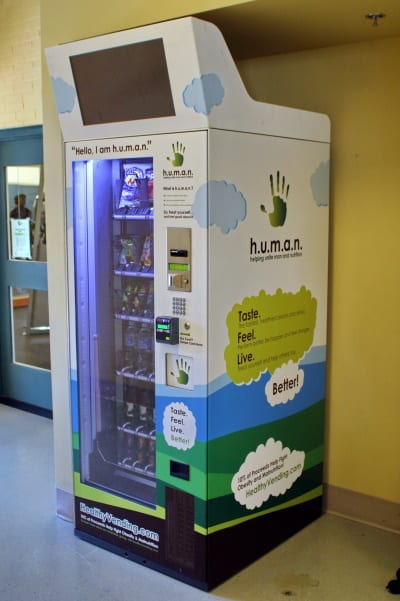 "A vending machine called ""h.u.m.a.n"" with a white background and a dark green cloud saying, ""Taste Feel Live."""