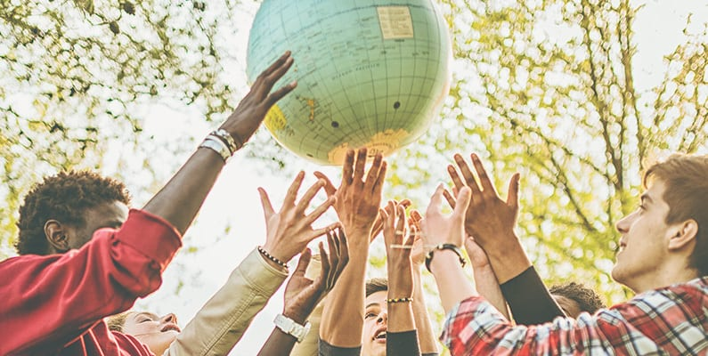 A group of people holding up a globe together.