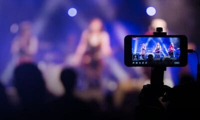 A student with his or her selfie stick recording a video of three rock artists at a concert.