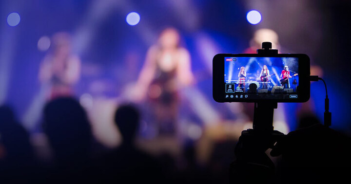 A student is recording a livestream concert with his or her phone.