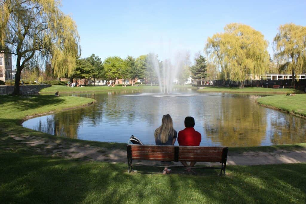 A man and a woman sitting on a bench at a park overlooking a pond with a fountain in the middle