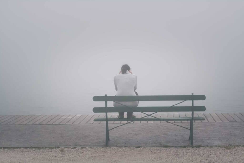 Woman, in intense fog, sitting on a bench holding her head in her hands