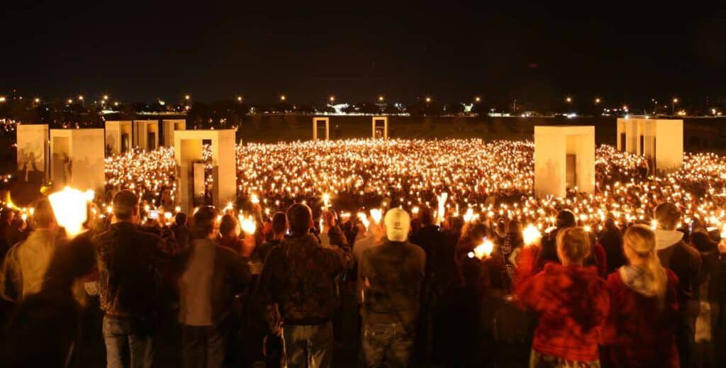 Thousands of people holding up candles at a Texas A&M bonfire