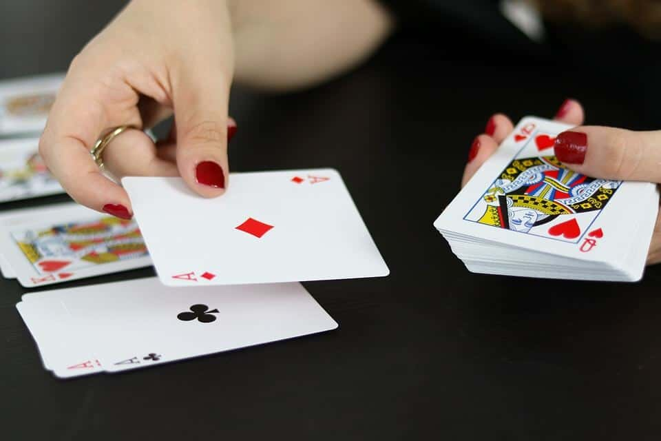 An elder lady  with a ring on her finger places her hand on the red Ace card, and her other hand is on a big stack of cards.