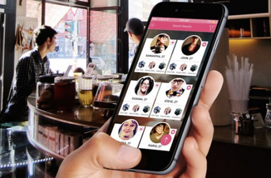 A person showing a dating app on his or her phone with six profile picture icons of people, while at a bar.