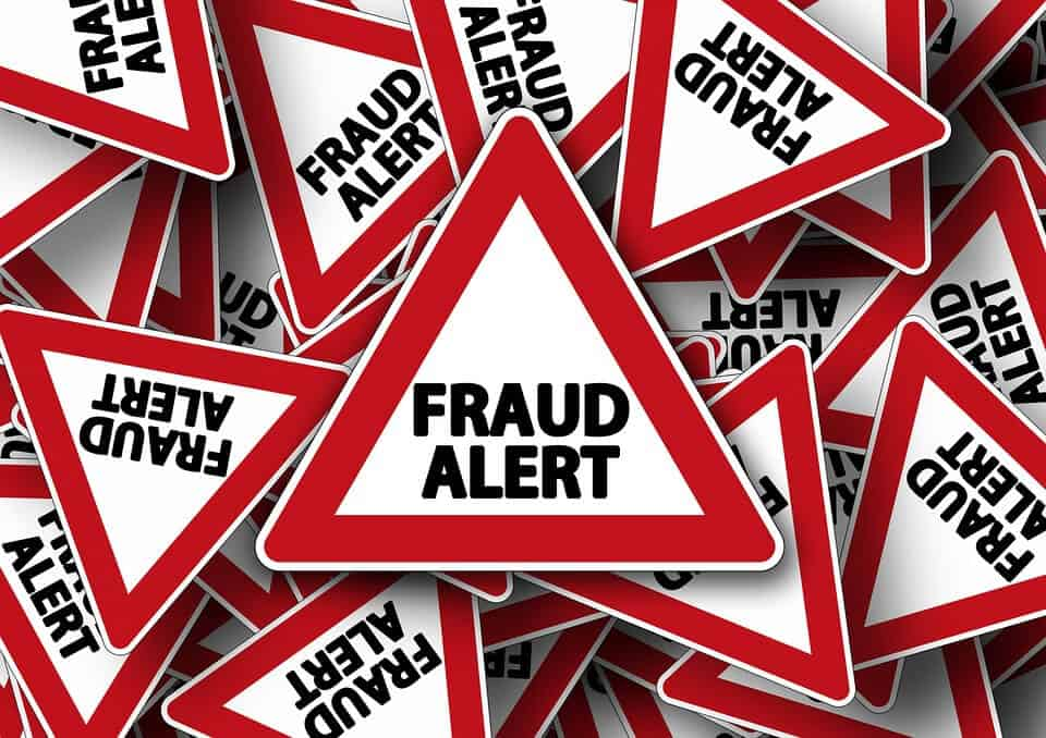 "A triangular shaped sign with a red outline saying, ""FRAUD ALERT."""