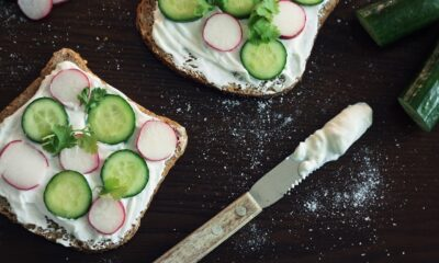 Two pieces of toast with white spread, cucumbers, and radishes on top.