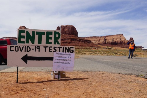 "A sign in a desert that contain green and black text saying ""ENTER: COVID-19 TESTING"", followed by a note with a construction worker on the far right."