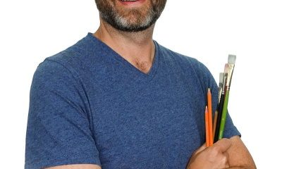 Matt Fussel wearing a blue shirt, holding paint brushes, in front of a white background.