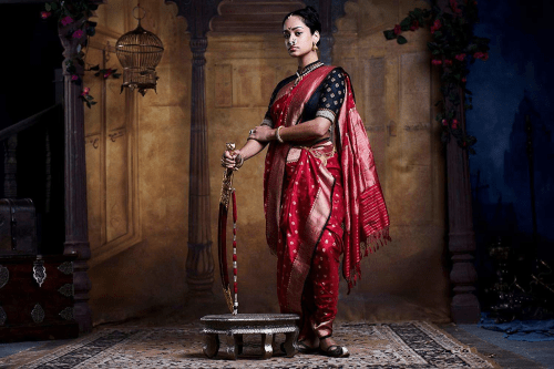 Devika Bhise wearing a colorful red and black shirt with designs on it, while standing next to a foot stool carrying a tool.