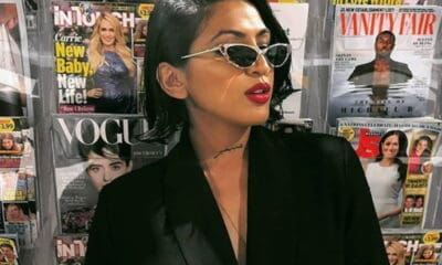 Dark-haired Maria Qamar with sunglasses wearing a black jacket standing in front of a big magazine stand with several magazines.