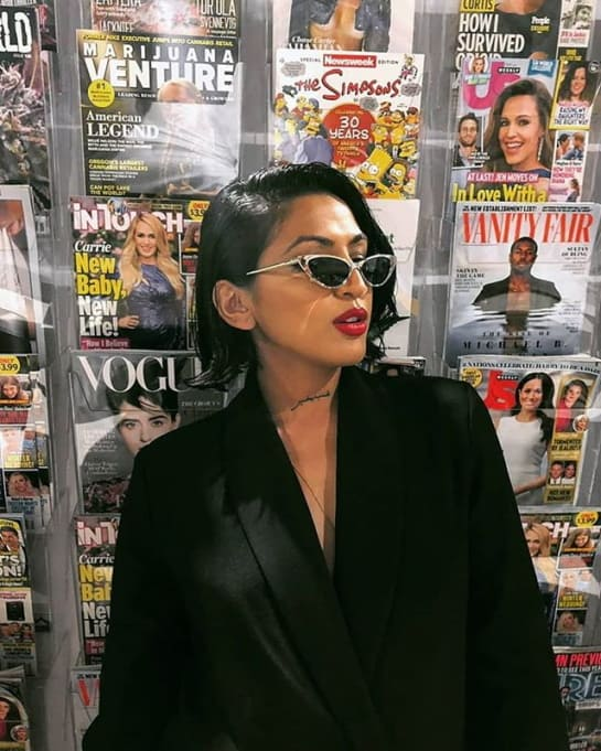 A young dark-haired lady with sunglasses wearing a black jacket standing in front of a big magazine stand with several magazines.