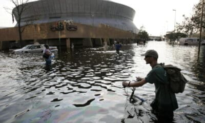 A man with a hat and green shirt and a backpack and a bike with three other isolated people, try to navigate through a flooded parking lot.