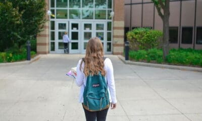 A young brunette girl, wearing a grey sweater and a blue backpack, and jeans, walking to her university.