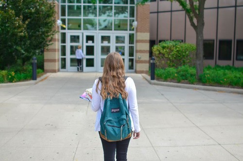 A young brunette lady wearing a grey sweater and a blue backpack with a logo on it and jeans walks to her university.