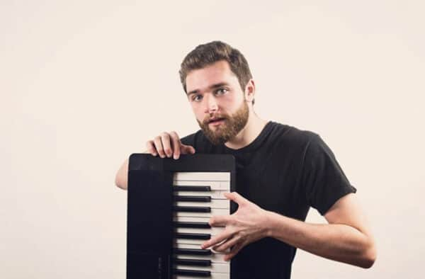 Kyle, posing in front of the camera in a black shirt while holding up a portable keyboard.