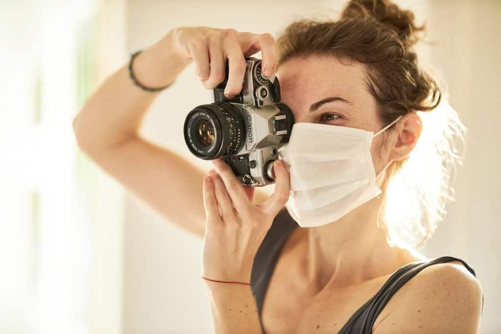 Woman wearing a mask, taking a photo