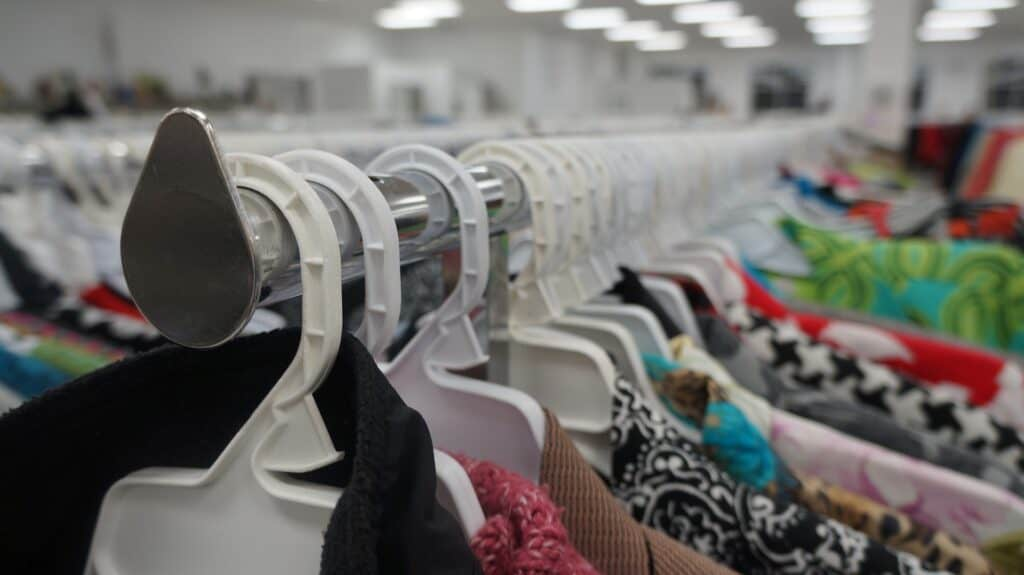 A close-up view of a rack filled with several pieces of clothing on white hangers at a thrift store.