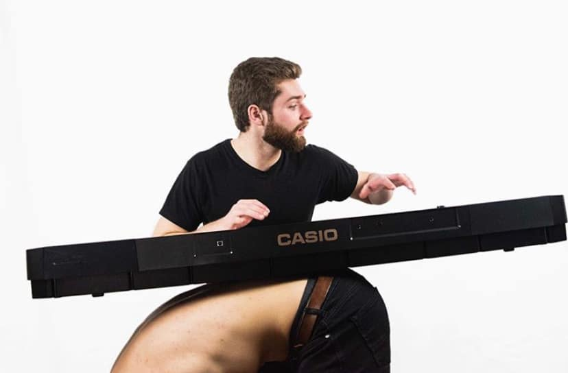 Kyle in a black shirt, balancing a keyboard on a persons back as they are bent over.