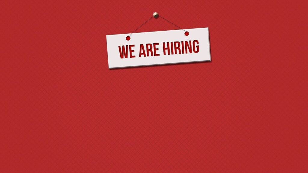 "Sign being held up on a red background stating ""WE ARE HIRING"""