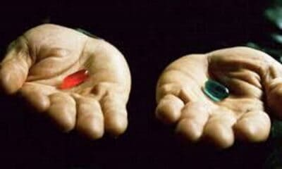A person holding a red pill in the right hand, and a green pill in the left hand.