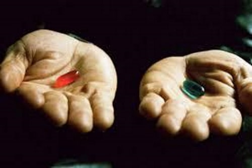 An older person with a red pill in one hand, and a green pill in another hand in a dimmed room.