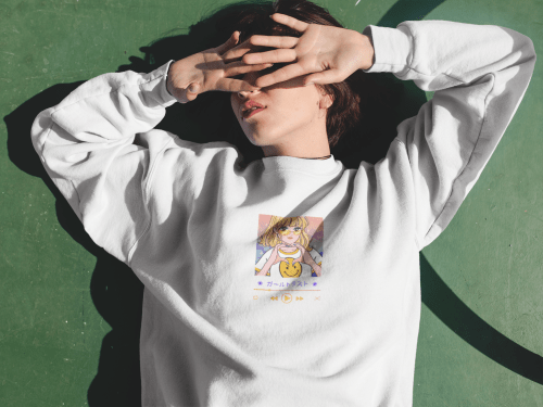 Young short-haired girl lying in the sun covering her eyes, while wearing a white crew neck sweatshirt with an anime picture.