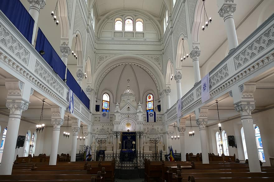 Inside a synagogue with white walls and pillars, with rows of wooden pews.