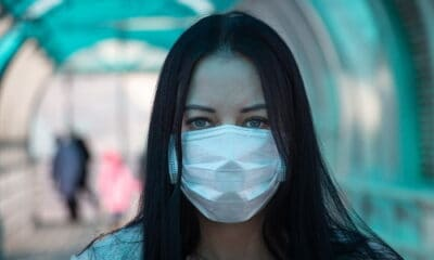 A dark-haired young lady wearing a blue sweater, and a white mask indoors.