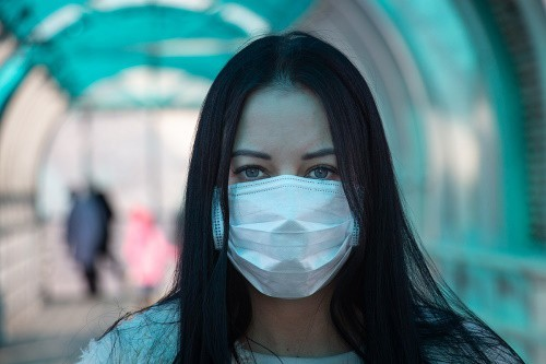 A dark-haired woman wearing a white medical mask.