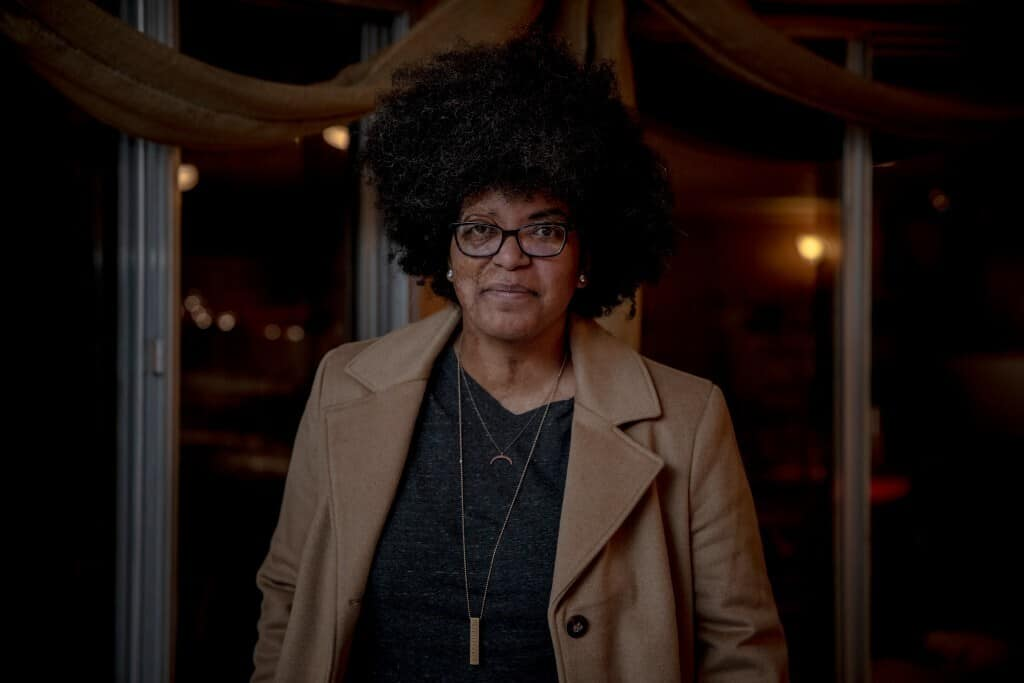Ash Lee Henderson with big dark curly hair and glasses wearing a beige jacket, with a grey shirt and jewelry while standing in a building with long beige drapes and windows.