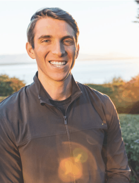 Brett Hagler with short grey hair wearing a grey sweater with the collar slightly opened smiling in front of the camera outside by the lake.