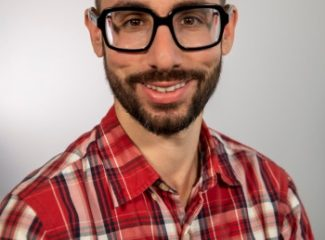 LSAT Unplugged coach Steve Schwartz with buzzed hair, glasses, a mustache and a beard wearing a red and white striped shirt standing in front of the camera.