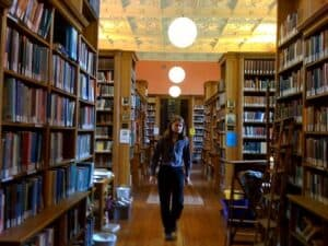 Person in a blue sweater and dark pants walking in between rows of book shelves in a library towards the camera