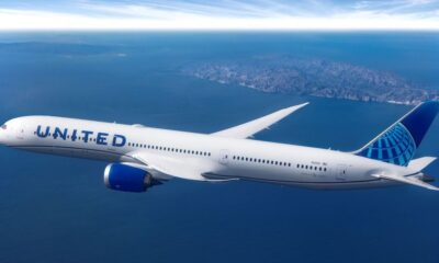 Airplane for United Airlines flying over a vast landscape with human settlement far off in the distance