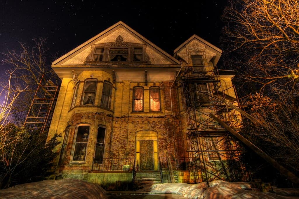 A big haunted house surrounded by trees.